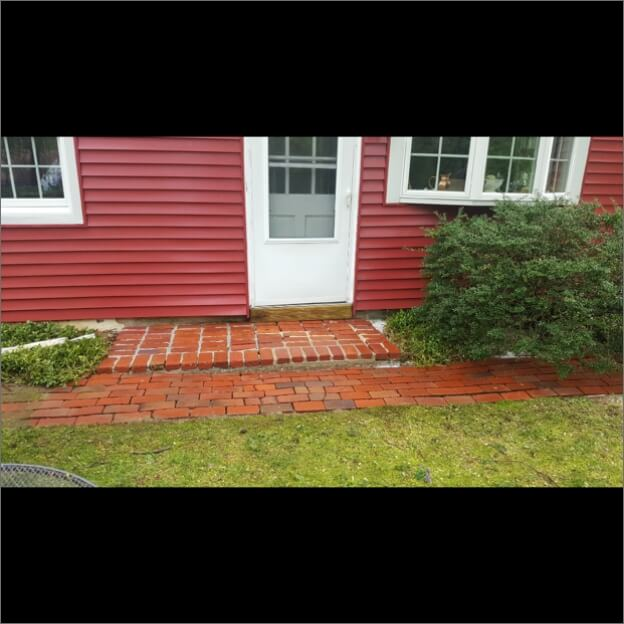 A shiny and vibrant brick walkway after a powerwash