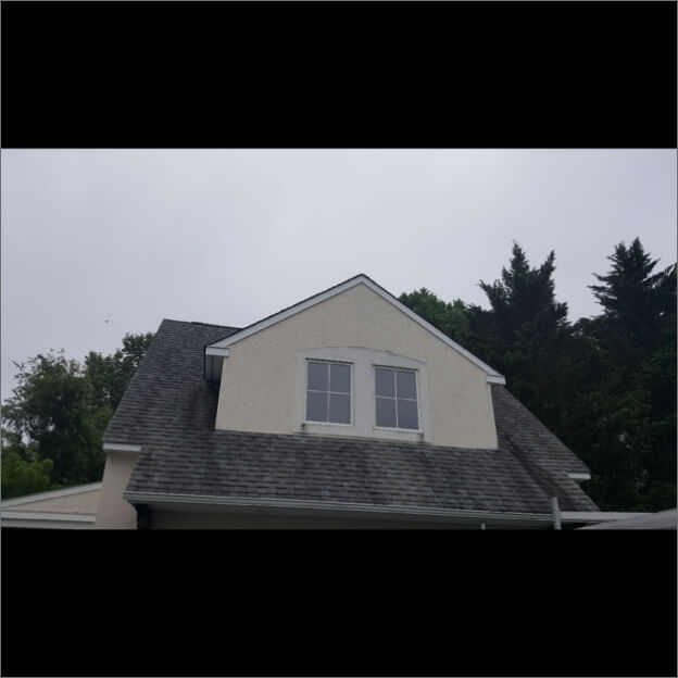 A dirty roof with streaked, dark brown shingles