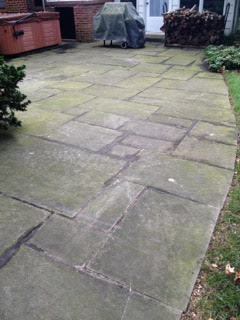 Dull stone patio coated in grime