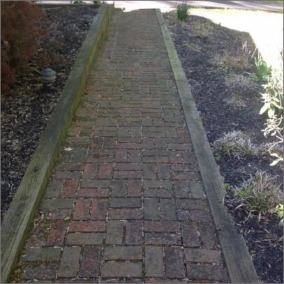 Brick walkway that's brown and dusty before wash