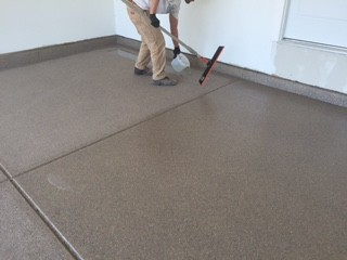 A person coating a concrete floor.