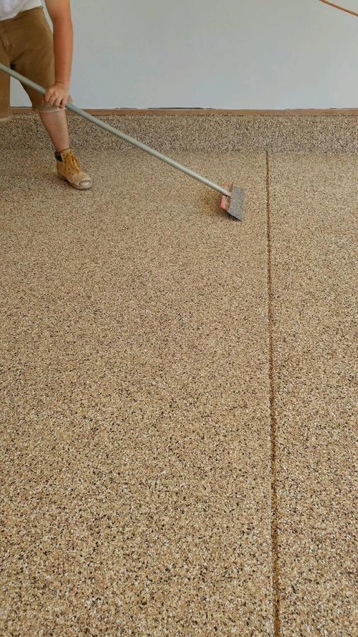 A person coating concrete.