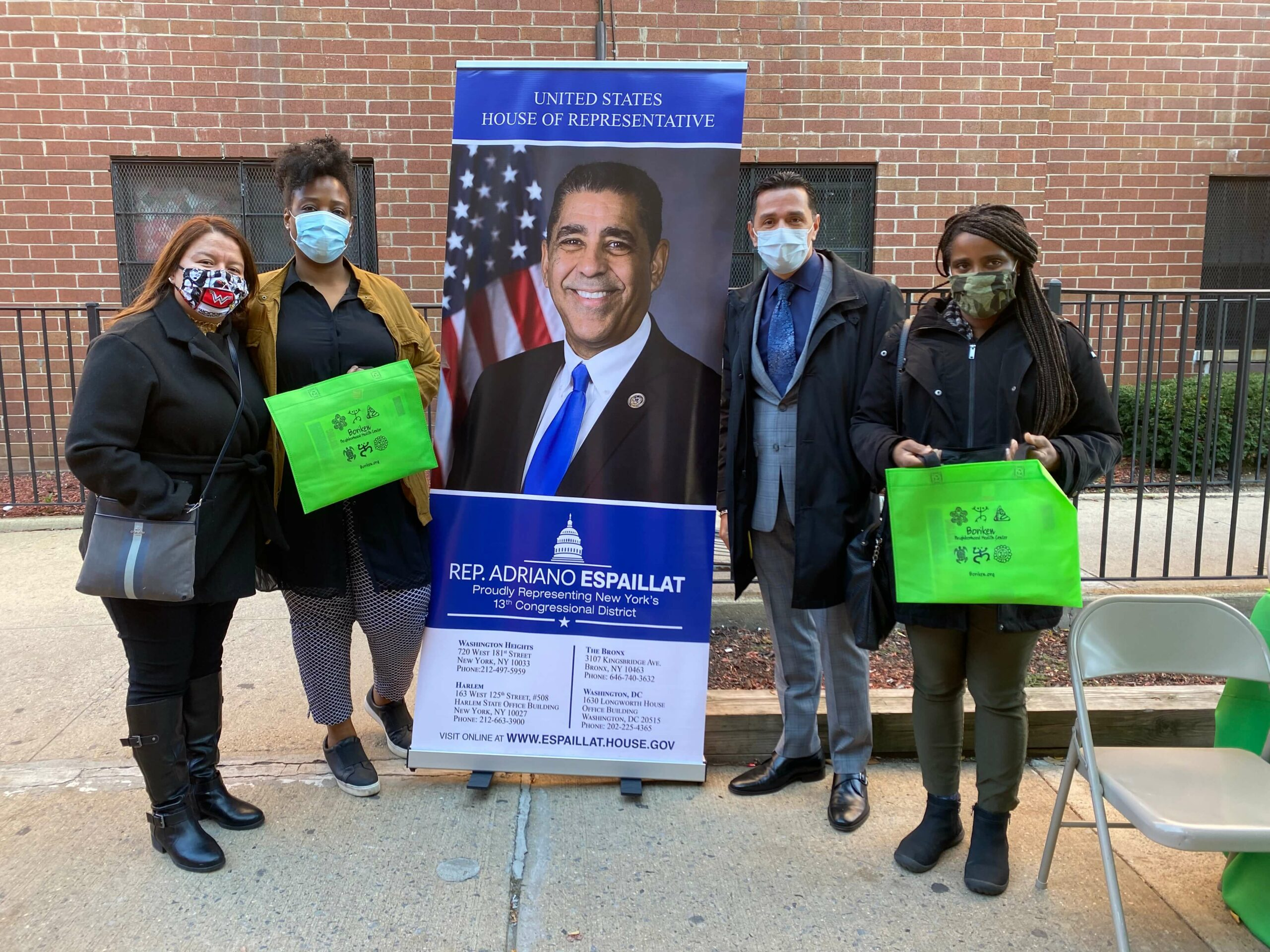 People posing with a photo of congressman Espaillat