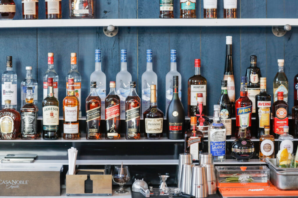 a selection of vodka, rum, whiskey, and other liquors behind the bar