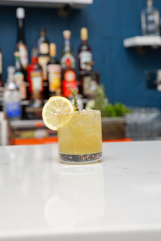 a refreshing cocktail served with a lemon slice