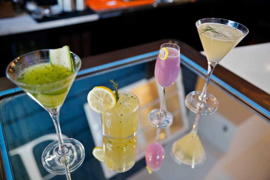 four cocktails laid out on a mirrored bar surface