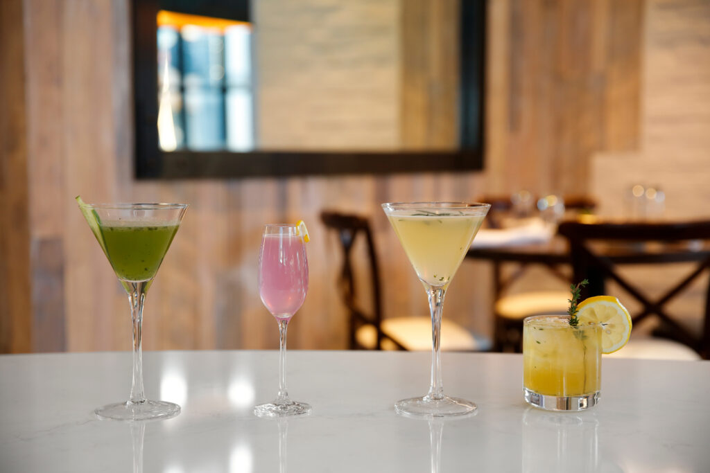 Green, pink, tan, and yellow cocktails lined up on top of a white bar top