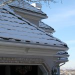A snowy roof with gutter protection covers over the gutters.