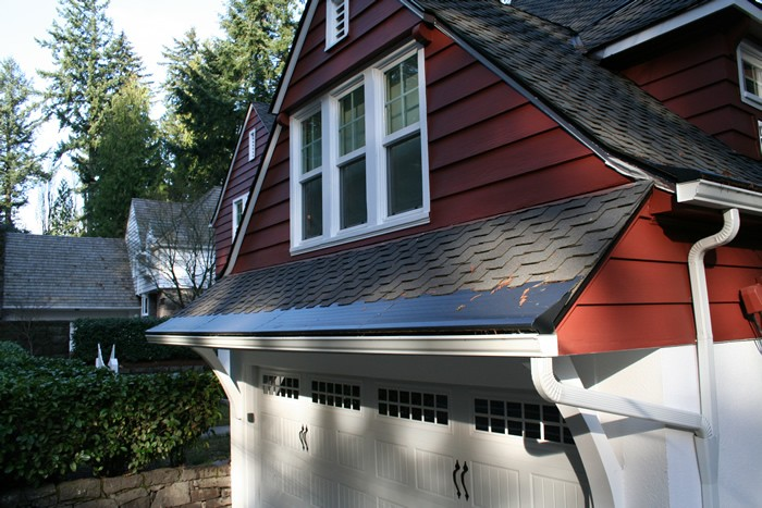 A gutter protection cover in context over a set of gutters.