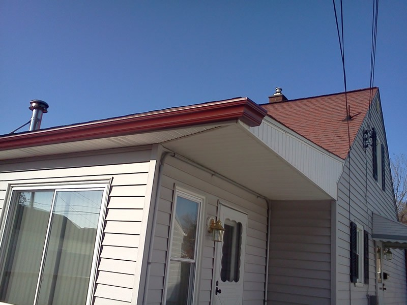 Red profile gutters at the edge of the roof of a house.