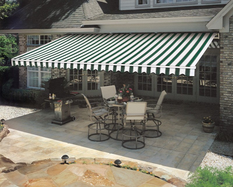 A retractable awning deployed over a back-yard gathering area.