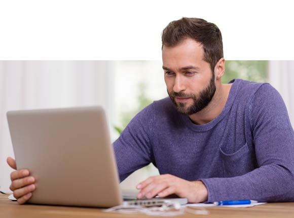 a man in a purple shirt working on a computer
