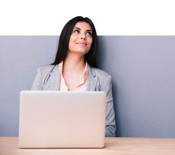 a smiling, black haired woman sitting at a computer looking up