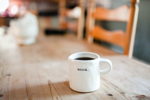 """a coffee cup that says """"begin"""", symbolizing a start to marketing your new business"""