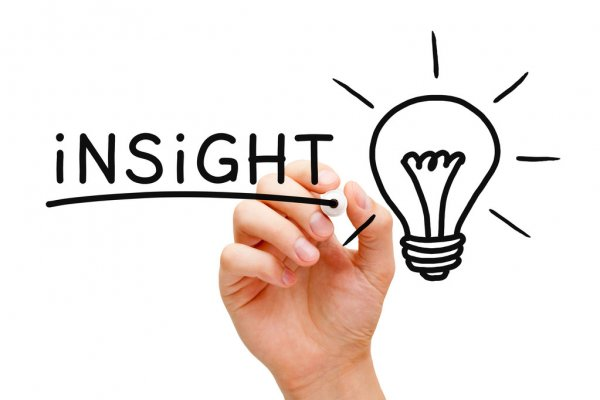 a person writing insight and a graphic of a lightbulb