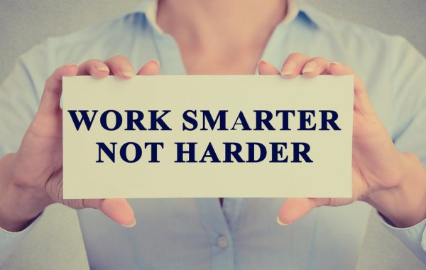 """a person holding a sign that says """"work smarter not harder"""""""