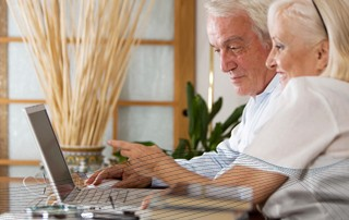 An elderly couple using a laptop.