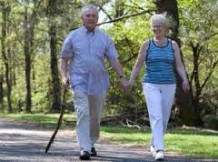 An elderly couple out for a walk, one holding a cane.