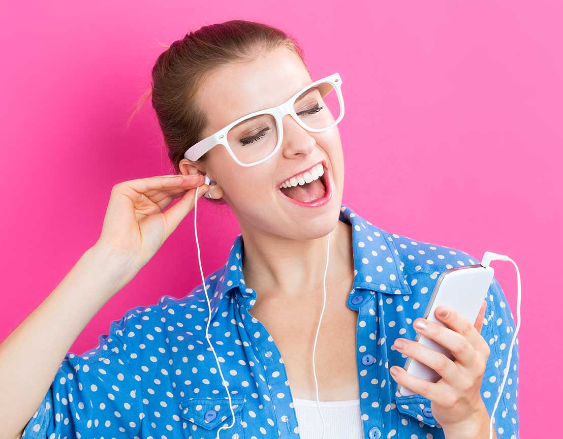 Happy young woman with earbuds on a pink background.