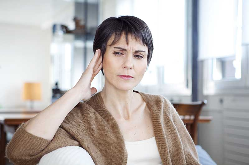 A woman experiencing symptoms of tinnitus.
