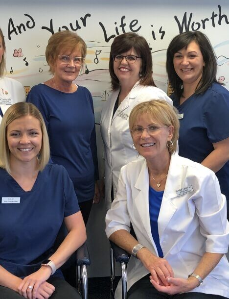 A group of six smiling woman, the three doctors and three support staff