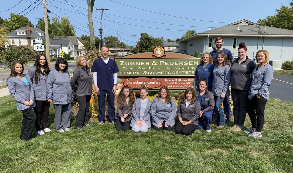 Doctor and team of 14 take a photo in front of Zugner & Pedersen sign
