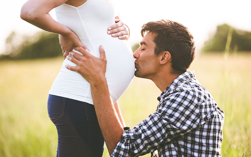 Pregnant Woman With Father kissing her stomach.
