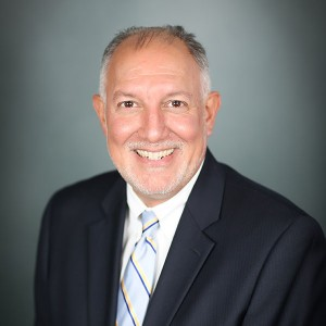 Carlos Santos, M.D., a man with grey hair and a beard, wearing a black suit