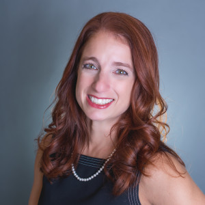 Lynn-Marie Aronica, M.D., a red-haired woman wearing a blue dress.