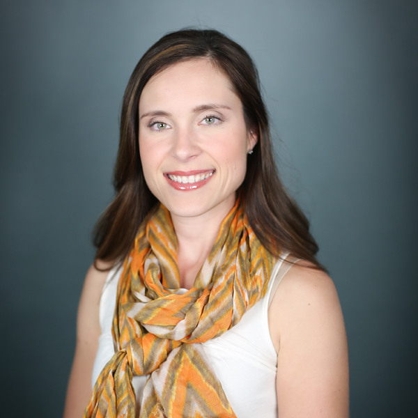 Jennifer Rojek, M.D., a brunette woman wearing an orange and green patterned scarf over a white sleeveless shirt.