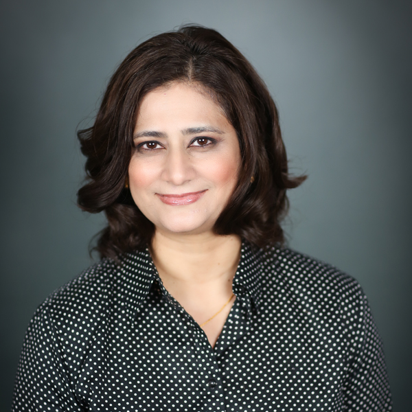Afshan Samad, M.D., a brunette woman wearing a black and white polka-dot shirt.