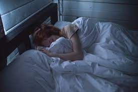 a healthy adult woman sleeping in a comfortable bed in the dark