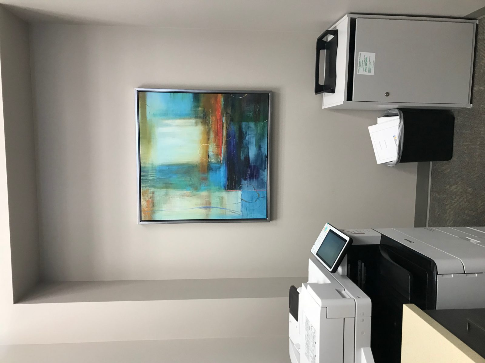 framed artwork in an office right by a copier machine