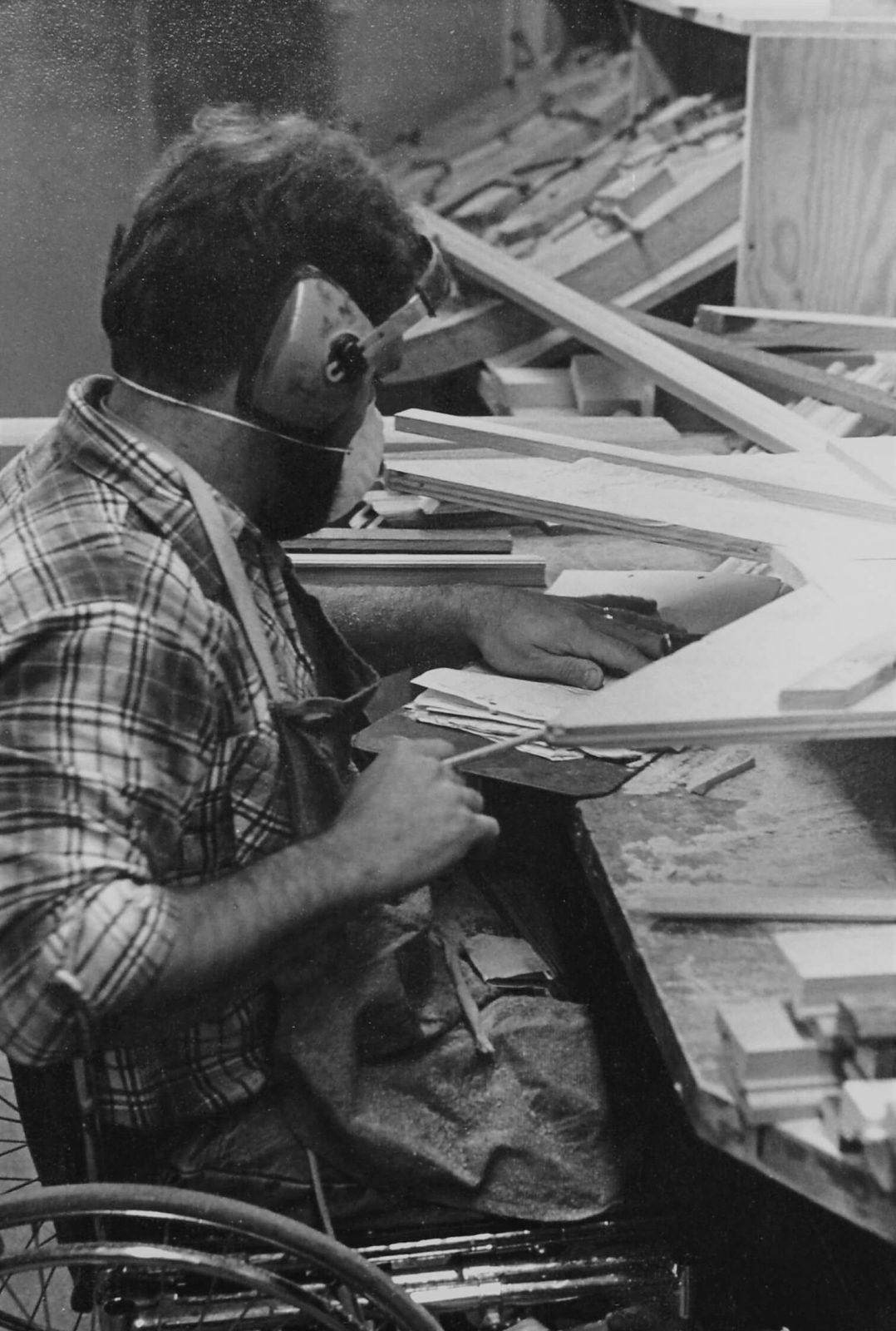 A young Ed Rider, wearing a dust mask and goggles, working on building a wooden frame.