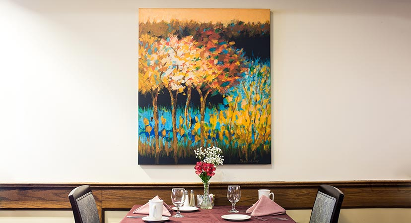 a painting hung on the wall above a dinner table