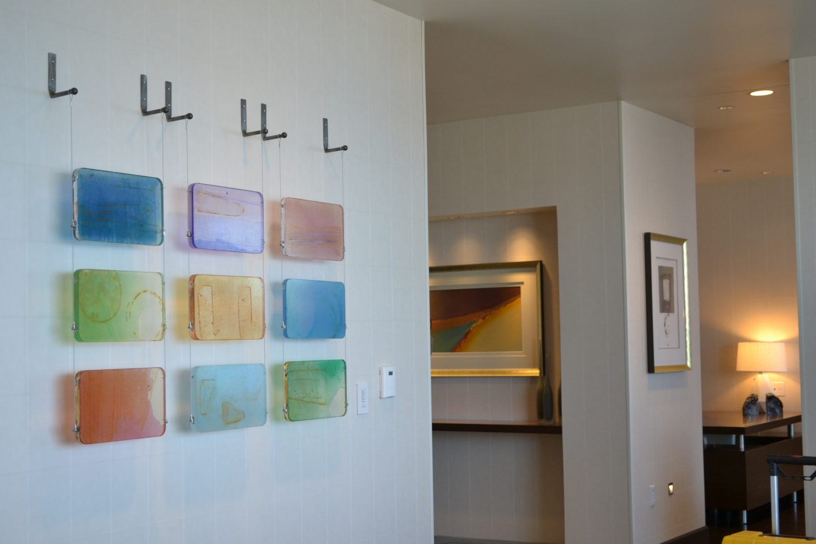 different pieces of artwork and framed paintings on the wall of a hotel room