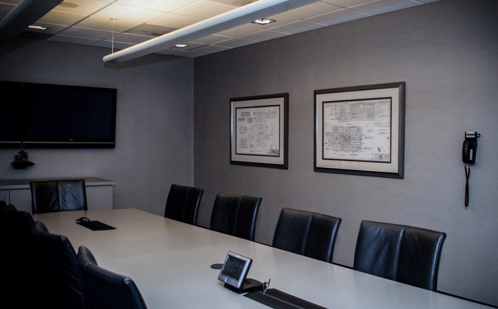 framed blueprints on the wall of a conference room