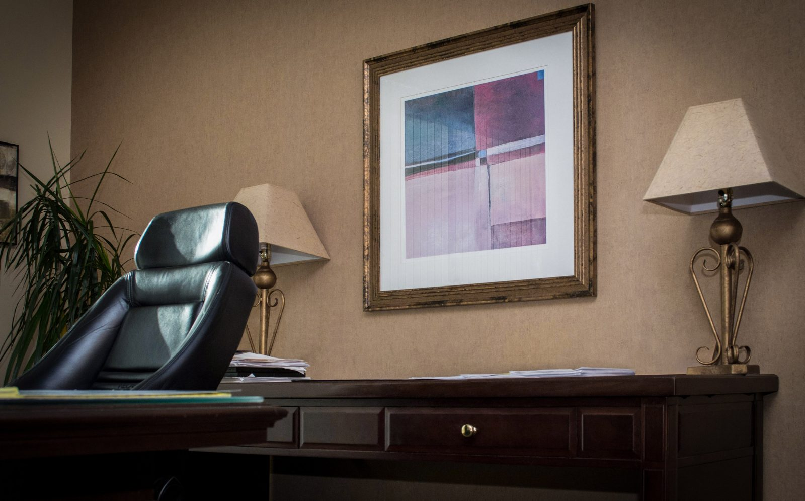 a framed painting on a desk between two lamps