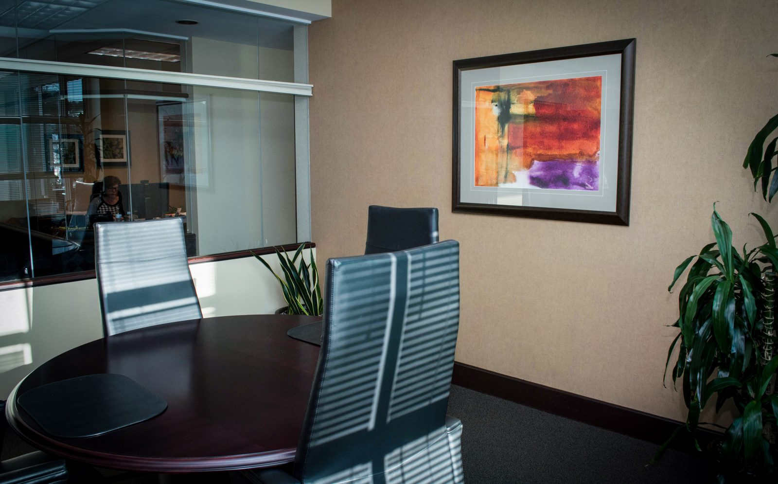 a framed painting on the wall of an office building with vacant chairs