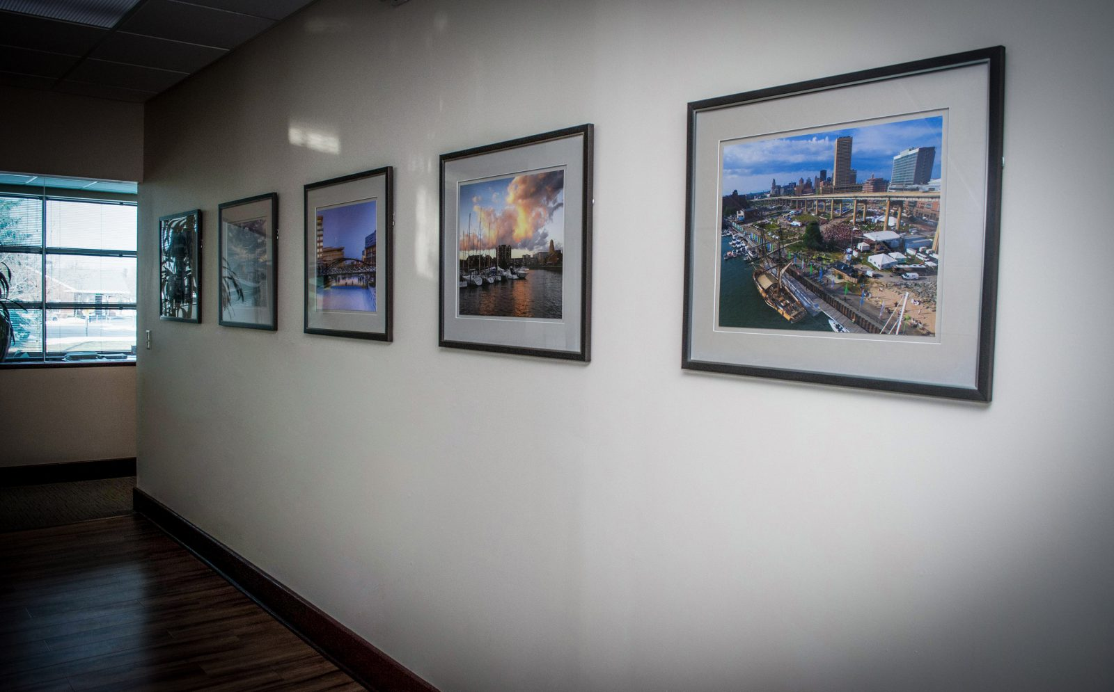 framed photos of cityscapes on the wall of an office