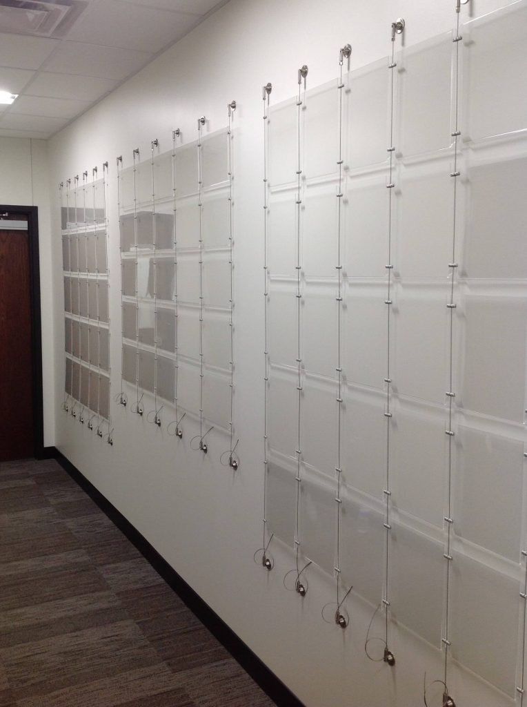 A grid of acrylic print holders attached to a wall