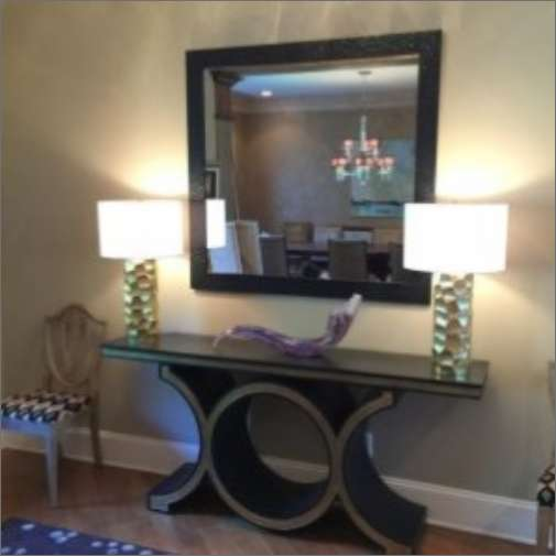 A lovely framed mirror on a wall with a small table in front of it