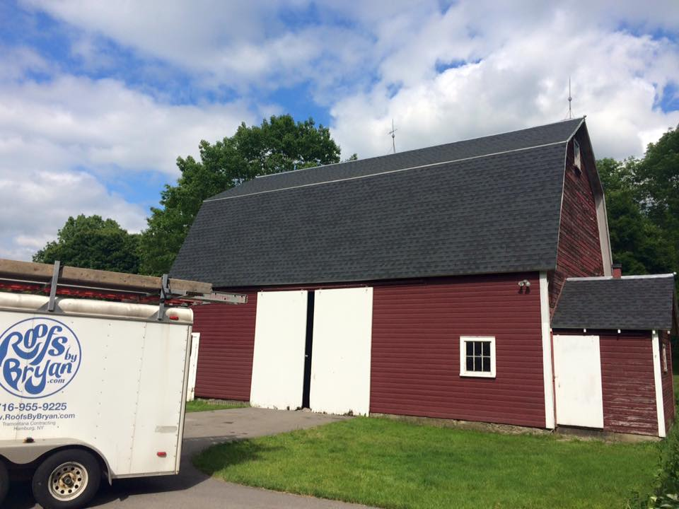 A barn with a Roofs by Bryan truck out front.