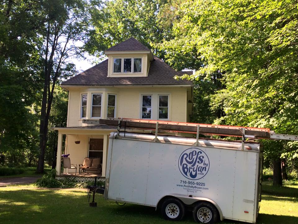 A Roofs by Bryan trailer out front of a house with bay windows and a new roof.