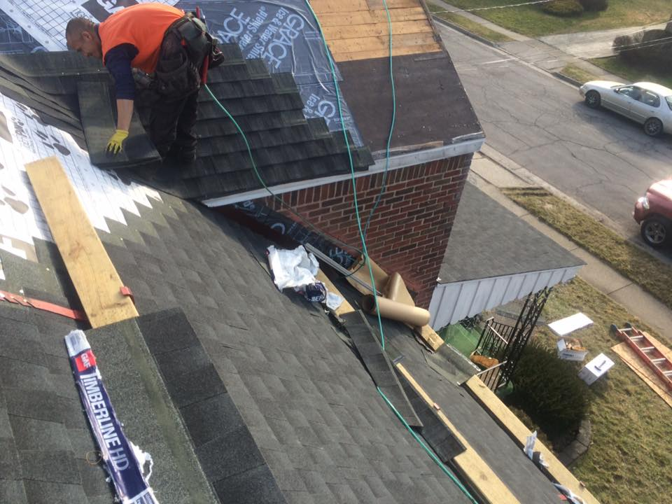 A person working on the corner of a roof.