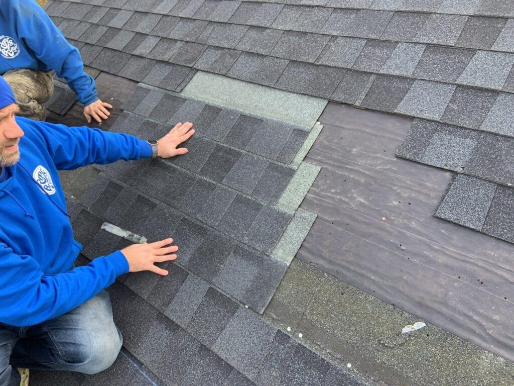 Our roofers repairing a damaged roof