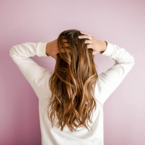 the back of a woman with long wavy hair