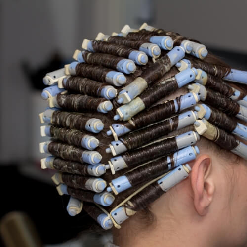 a woman with a lot of curlers in her hair