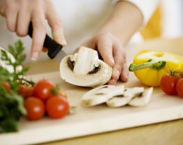 Woman chopping vegetables on a wooden cutting board
