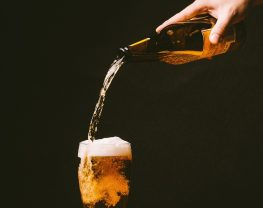hand pouring beer into glass